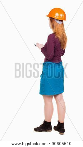 Backview of business woman in construction helmet stands and enjoys tablet or using a mobile phone.   Isolated over white background. Girl keeps a record of the work using the Tablet PC.