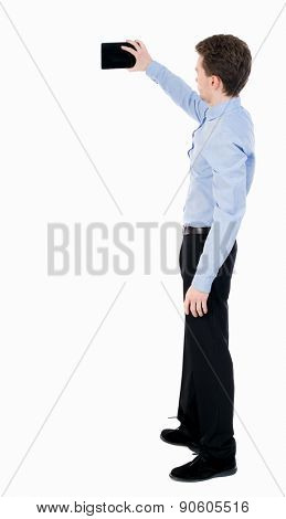 back view standing business man with tablet computer in hands of. Rear view people collection. backside view person. Isolated over white background. guy in office clothes photographed on a Tablet PC.