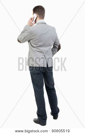 back view of business man in suit  talking on mobile phone.    rear view people collection. Isolated over white background. backside view of person. Businessman solves the case by telephone.