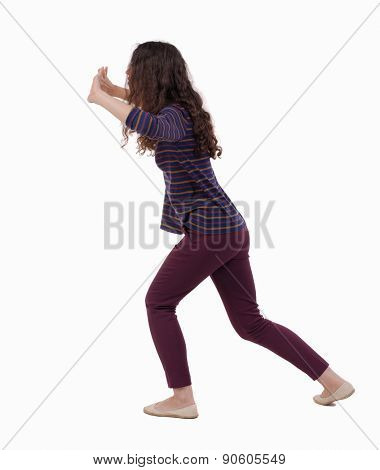 back view of woman pushes wall. Isolated over white background. Rear view people collection. backside view of person.  Girl in red jeans exposed open palms in front of him.