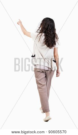 back view of walking  curly woman. beautiful girl in motion.  backside view of person.  Rear view people collection. I Girl in brown trousers to go see something interesting and shows.