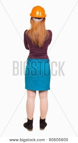 Backview of an woman engineer in construction helmet stands. Standing young woman. Rear view people collection.  backside view of person.    Young girl crossed her arms over her chest and watches