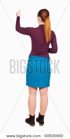 back view of woman. Young woman in vest presses down on something. Isolated over white background. backside view of person. she holds his hand open, palm forward. Red-haired girl approves.