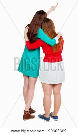 Two long haired friendly women pointing .  backside view of person. Isolated over white background. Rear view people collection. Two girlfriends in summer skirts are hugging and looking at something.