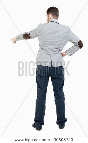 Back view of pointing business man. gesticulating young guy in black suit. Rear view people collection.  backside view of person.  Isolated over white background. . Businessman points finger down