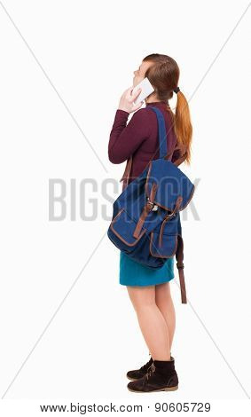 Back view of standing young woman with backpack speaks by mobile phone. Rear view people collection.  backside view of person.  Isolated over white background.