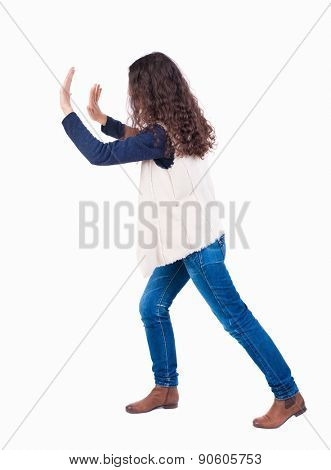 back view of woman pushes wall. Isolated over white background. Rear view people collection. backside view of person. curly girl put her hands on the obstacle.