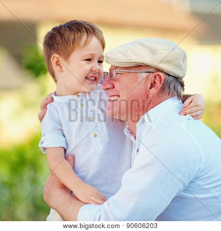 Portrait Of Happy Grandpa And Grandson Embracing Outdoors