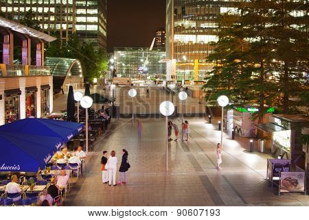 LONDON, UK - JULY 29, 2014: Canary Wharf square view in night lights with office workers chilling o