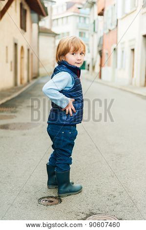 Outdoor portrait of a cute little boy, wearing blue waistcoat and rain boots