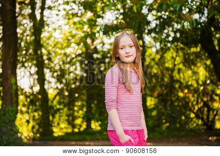 Portrait of a cute little girl of 7 years old in the park
