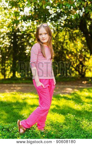 Vertical portrait of a cute little girl of 7 years old in the park
