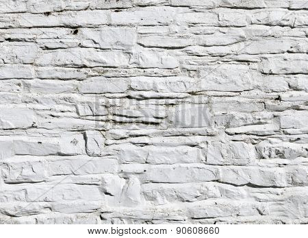 Whitewashed paint on stone wall close up.