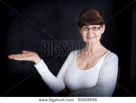 Mature good looking woman with open hand holding something blank