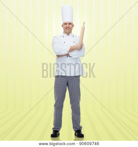 cooking, profession and people concept - happy male chef cook holding rolling pin over yellow background