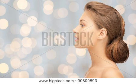 health, people, holidays, luxury and beauty concept - beautiful young woman face over lights background