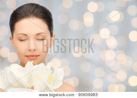 beauty, people, holidays and health concept - beautiful young woman smelling flowers with closed eyes over lights background