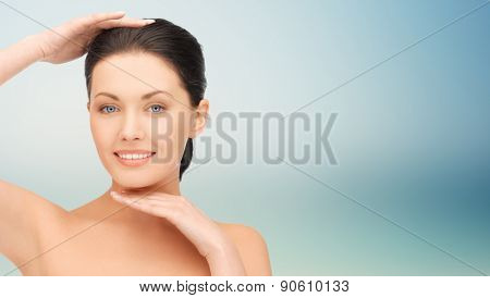 beauty, people, plastic surgery and health concept - beautiful young woman touching her face and chin over blue background