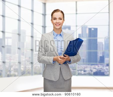 business, people, real estate and sale concept - smiling young businesswoman holding folder over office or empty city apartment background