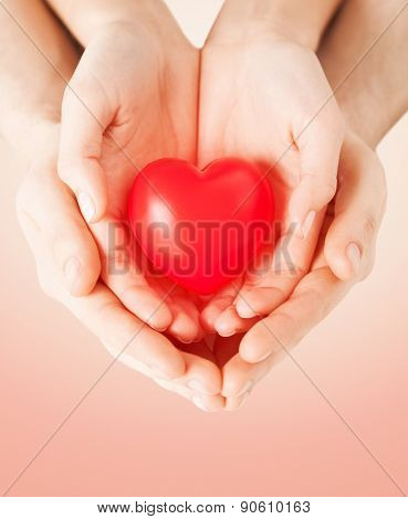 health, love and relationships concept - close up of couple hands with big red heart over beige background