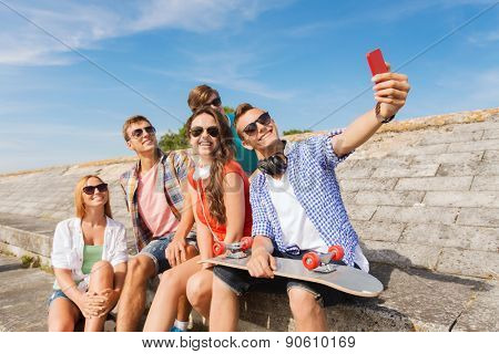 friendship, leisure, summer, technology and people concept - group of smiling friends with skateboard and smartphone making selfie outdoors