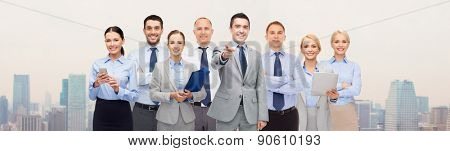 business, people, corporate, teamwork and office concept - group of happy businesspeople pointing at you over city background
