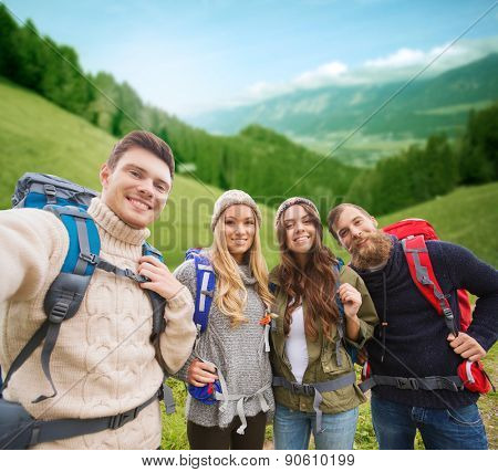adventure, travel, tourism, hike and people concept - group of smiling friends with backpacks making selfie over alpine hills background