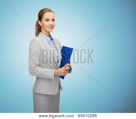 business, people and education concept - smiling young businesswoman with holding over blue background