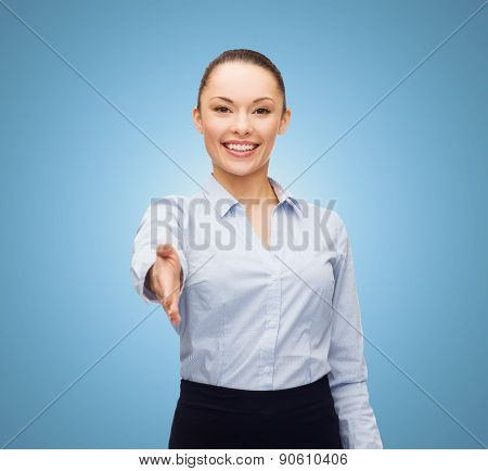 business, gesture and education concept - friendly young smiling businesswoman with opened hand ready for handshake over blue background