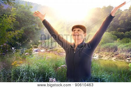 Sunrise, beautiful park and happy woman raising her hands up to the sun. Happy and healthy life conc