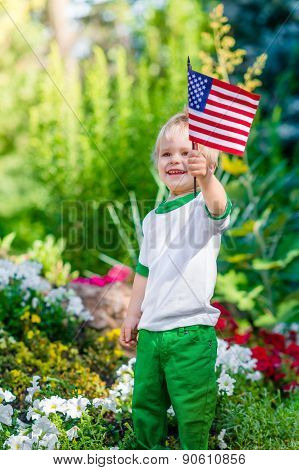 Smiling Blond Little Boy Holding American Flag And Waving It In Sunny Park Or Garden On Summer Day