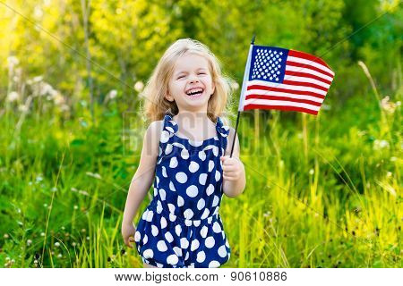Adorable Laughing Little Girl With Long Curly Blond Hair Holding American Flag And Waving It