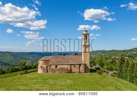 Old stone church on green lawn under blue sky with white clouds in spring in Piedmont, Northern Italy.