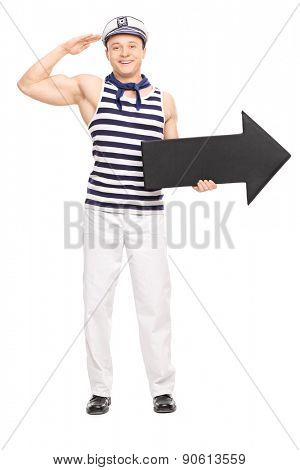 Full length portrait of a young male sailor saluting towards the camera and holding a big black arrow pointing right isolated on white background