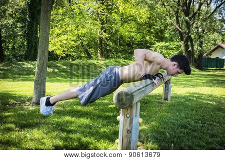 Attractive shirtless young man exercising outdoor in city park
