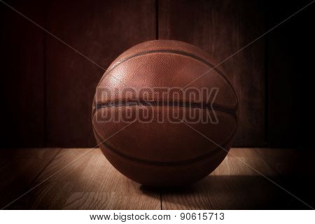 Vintage basketball on a wooden court background in the spotlight