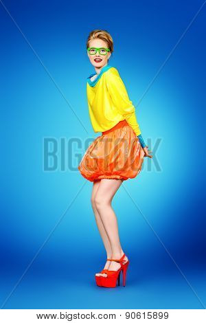 Full length portrait of a glamorous fashion model posing in vivid colourful clothes and glasses. Bright fashion. Optics, eyewear. Studio shot.