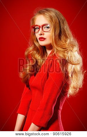 Beautiful young woman with magnificent blonde hair wearing red dress and elegant red glasses. Beauty, fashion. Optics, eyewear. Red background.