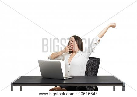 tired woman sitting with laptop and yawning over white background