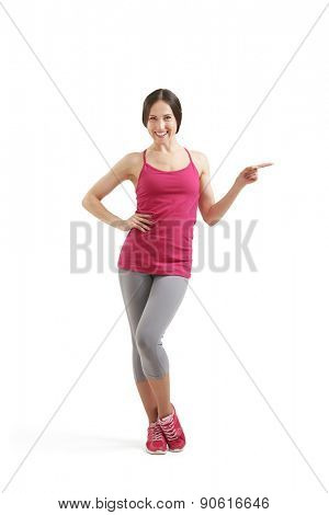 full-length portrait of smiley sportswoman in sportswear pointing forefinger at something. isolated on white background