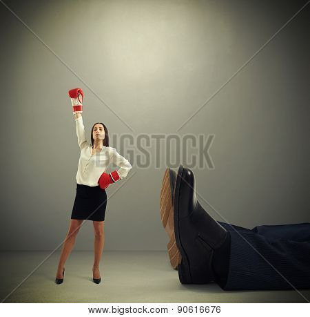 winner businesswoman in red boxing gloves standing near big lying mans legs over dark grey background