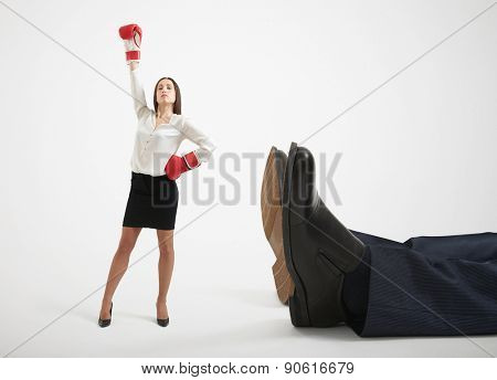 winner businesswoman in red boxing gloves standing near big lying mans legs over light grey background