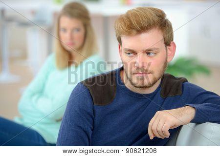 Couple sulking on a sofa