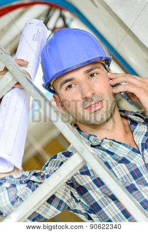 Builder on the phone by a ladder