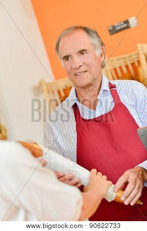 Baker serving a customer a baguette