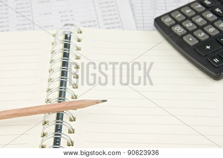 Pencil On Notebook With Calculator At Top Right