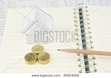 Pencil On Notebook With Gold Coin And House