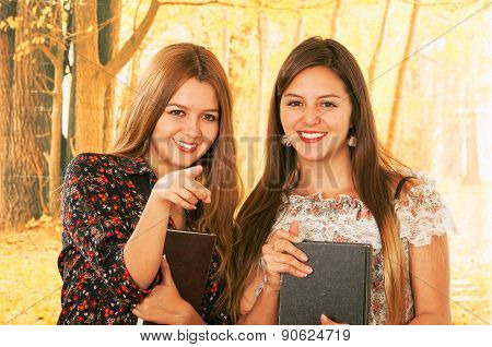 Two beautiful young college girls over fall background
