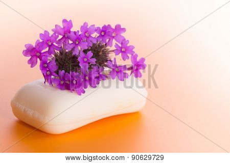 Soap with purple Prairie Verbena flower, on gradient orange background