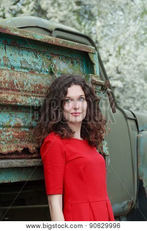 Blue-eyed Brunette Standing At Old Truck Body And Blooming Fruit Trees Background